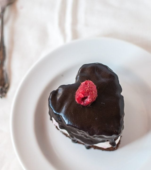 Mini heart-shaped chocolate cakes with fresh raspberry whipped cream and chocolate ganache