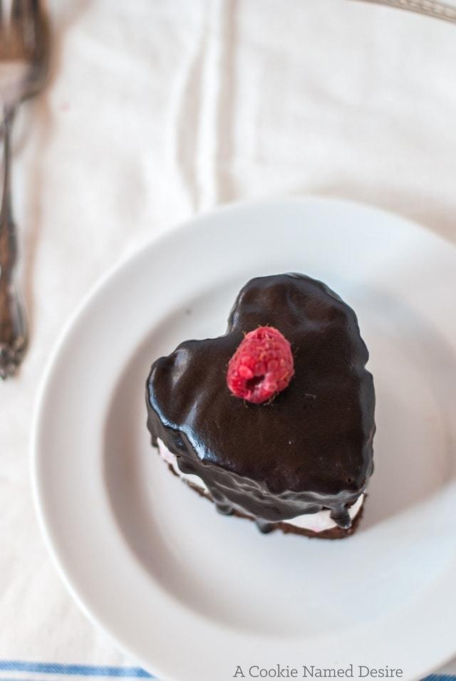 Mini heart-shaped chocolate cakes with fresh raspberry whipped cream and chocolate ganache