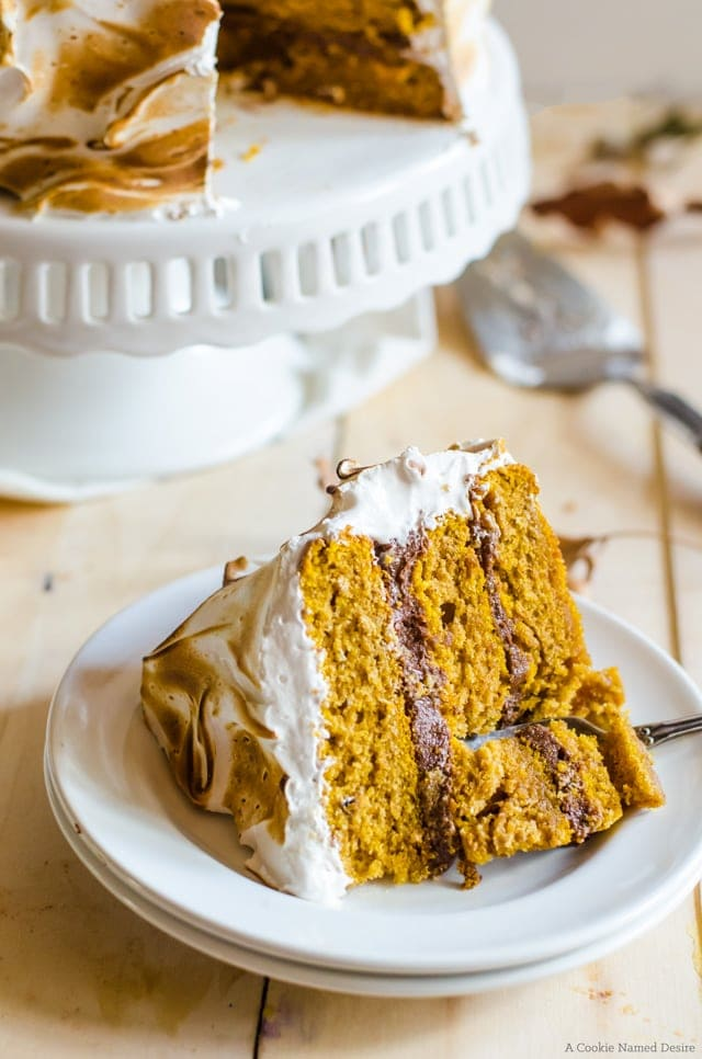 Enjoy a slice of this moist pumpkin cake with ginger chocolate frosting and toasted cinnamon meringue