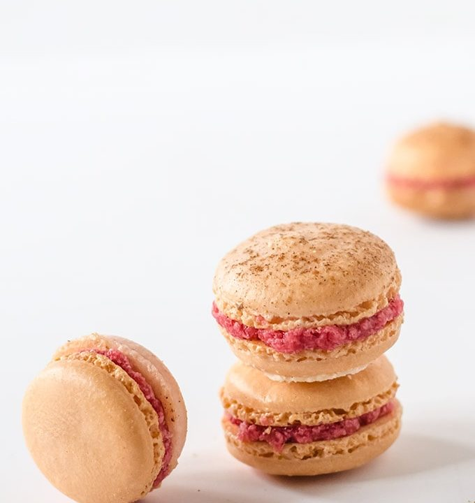 Mulled cranberry macarons. These macarons have a light dusting of cardamom and cinnamon and are stuffed with a deliciously sweet mulled cranberry buttercream frosting. The perfect holiday treat!