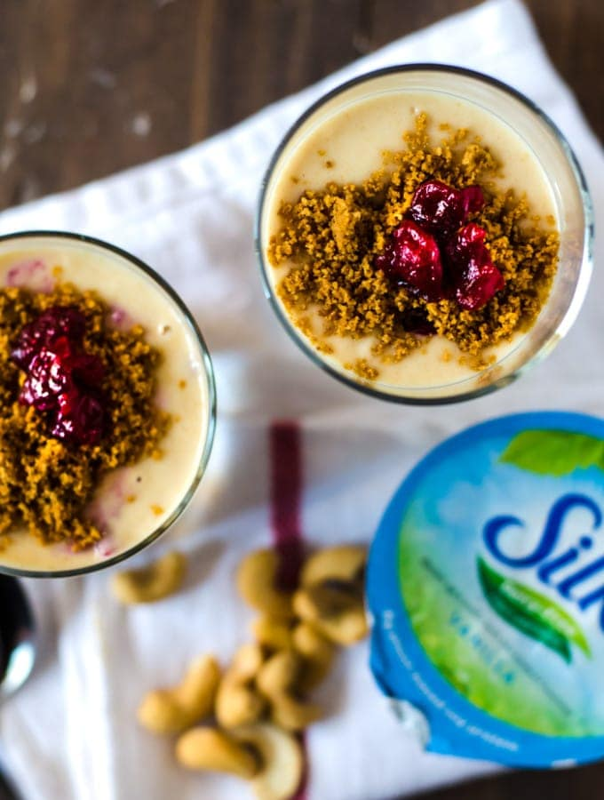 A creamy vegan no-bake cheesecake parfait with cranberry swirl and gingersnap crumble