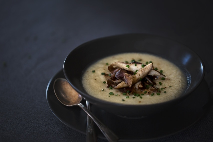A bowl of Creamy Cauliflower and Celery Root Soup with Roasted Shiitake Mushrooms is photographed from the front on a dark surface.