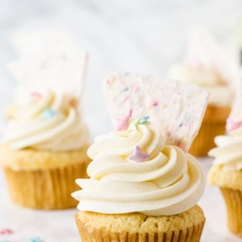 Celebrate Spring with these heavenly vanilla cupcakes filled with a bright lemon curd and topped with a fun sprinkle-filled white chocolate bark!