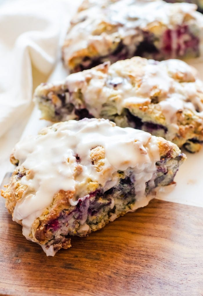 Tender mixed berry scones filled with blueberries, blackberries, raspberries, and strawberries then topped with a sweet vanilla glaze. Berry scones like these make excellent treats for breakfast, brunch, or with tea.