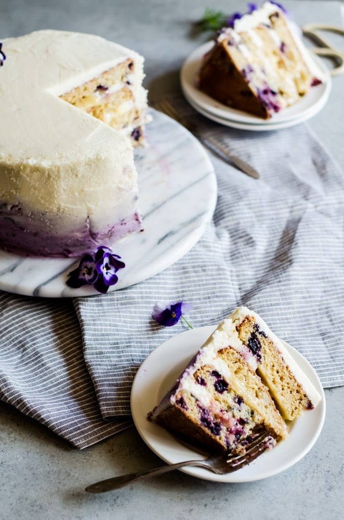 a delicious and beautiful lemon blueberry cake filled with lemon curd and frosting in ombre blueberry buttercream