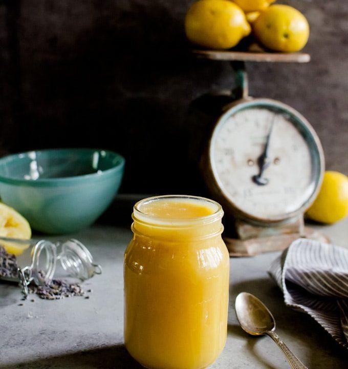 lemon curd in jar with lemons in background