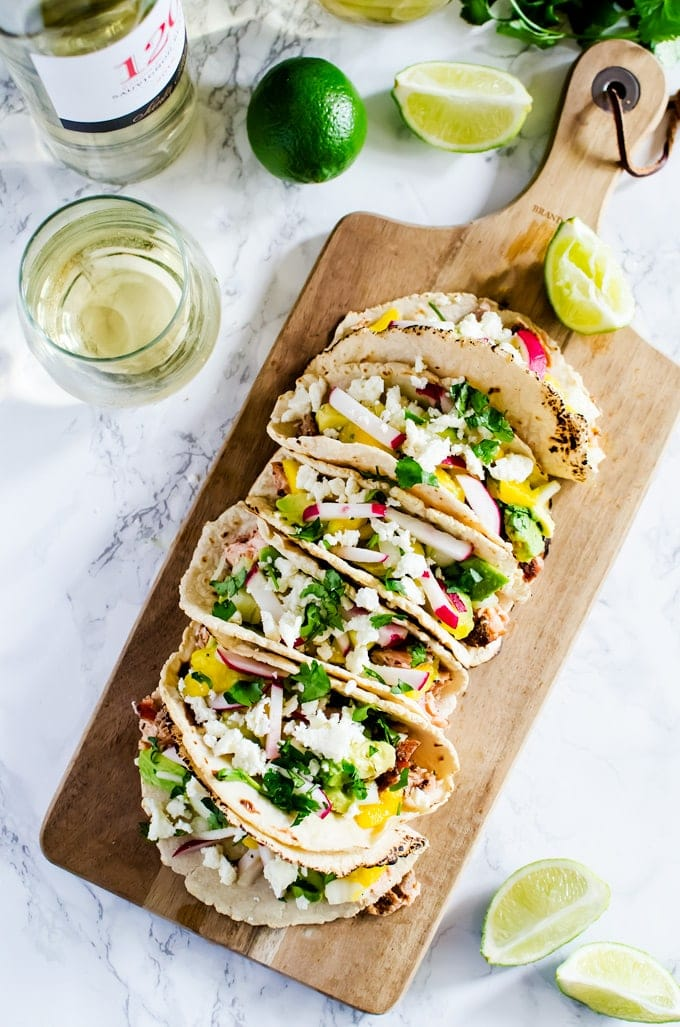Cedar grilled salmon tacos with a refreshing avocado mango salsa and homemade corn tortillas. The best thing you will make this summer.