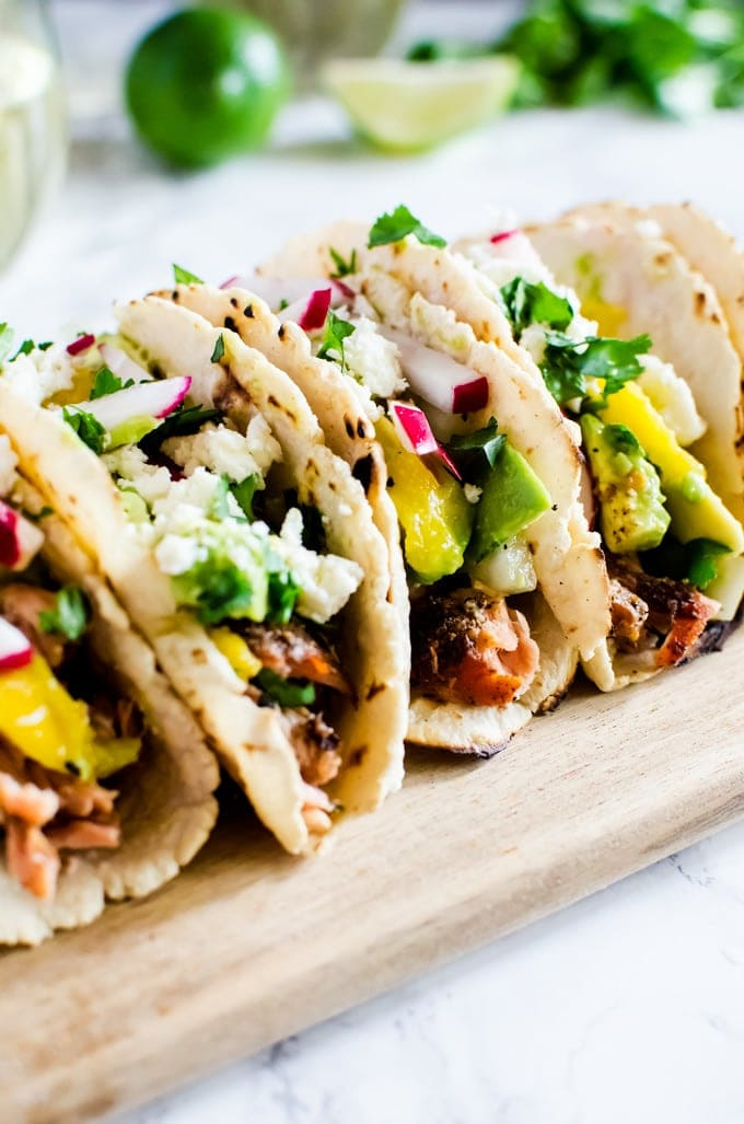 Grilled salmon tacos with a refreshing avocado mango salsa. If you only make one thing on the grill this summer, it has to be this.
