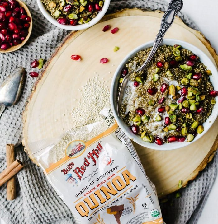 A deliciously healthy Persian love cake quinoa breakfast bowl flavored with rosewater, pistachios, and pomegranate