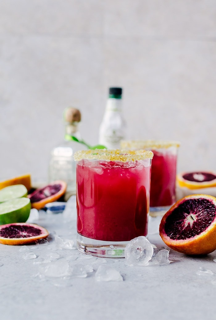 glasses of margaritas next to blood oranges and tequila