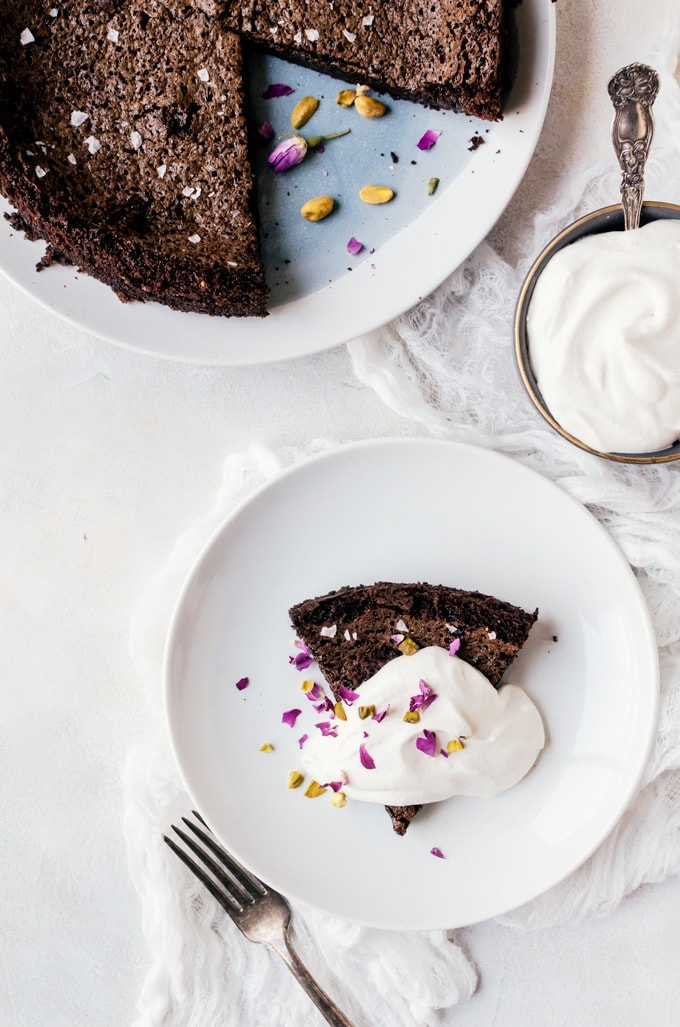 A rich chocolate olive oil cake with cardamom whip, pistachios, and rose for a truly decadent dessert