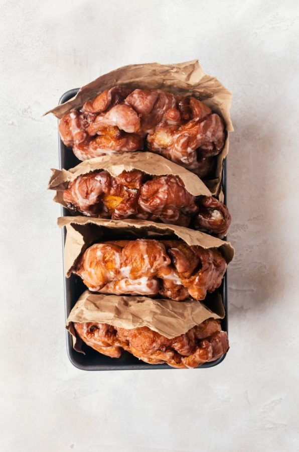 Irresistible peach fritters with cinnamon infused dough and coated in a sweet maple glaze