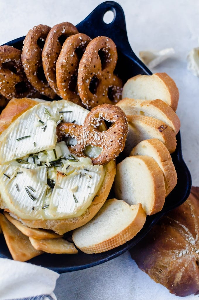 Rosemary garlic baked brie inside a crusy loaf of bread is the answer to all your appetizer woes