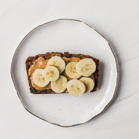 Slice of brown butter banana bread with peanut butter and sliced bananas on a plate