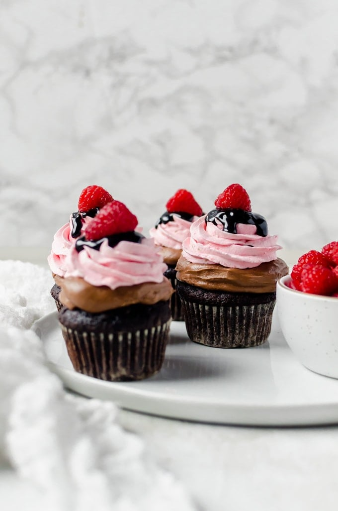 plate of nutella chocolate cupcakes with raspberry whipped cream and a bowl of raspberries