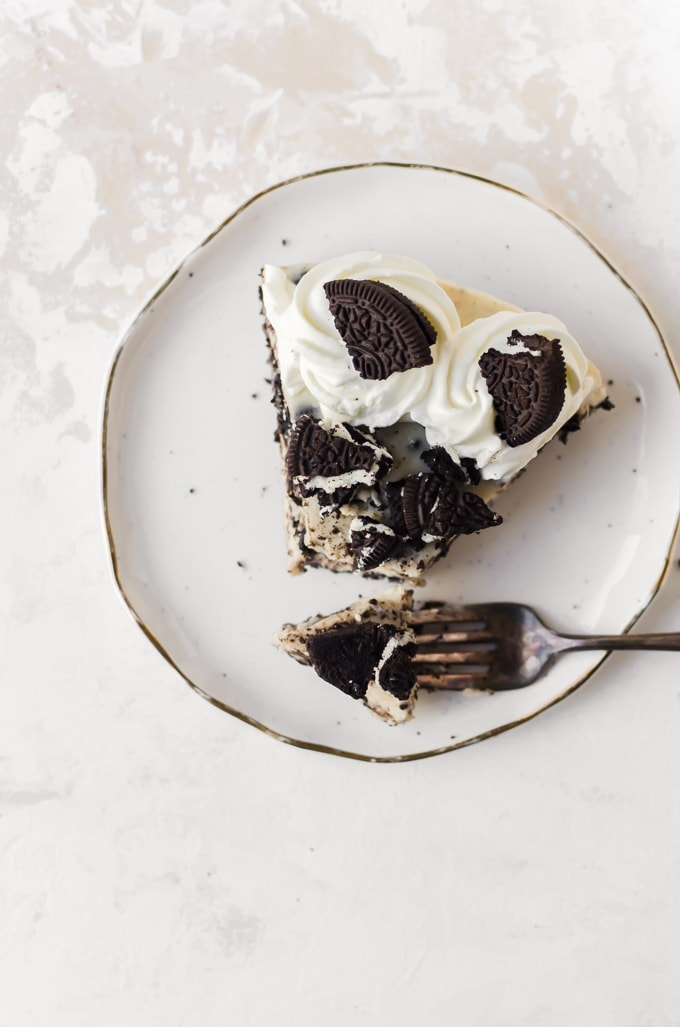 An ocerhead photo of a slice of No-bake Oreo Cheesecake on a plate with a forkful of cheesecake