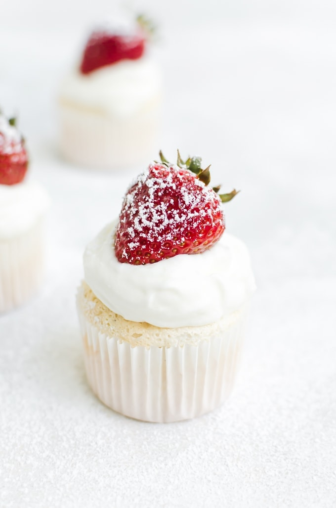 close up of cupcake topped with whipped cream, strawberry and powdered sugar