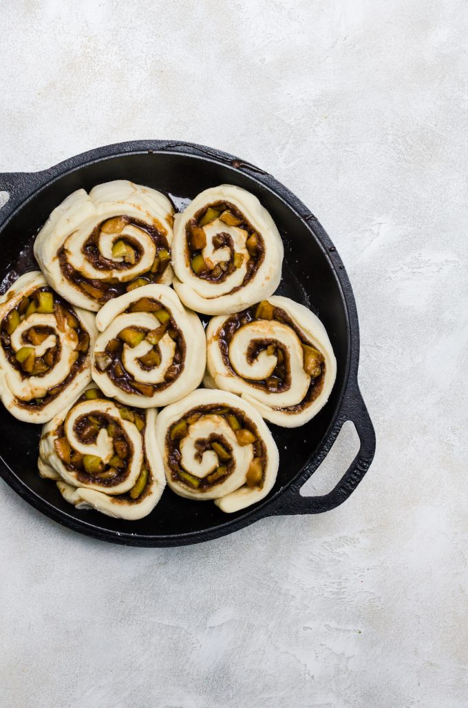 cinnamon rolls with apples in pan before baking