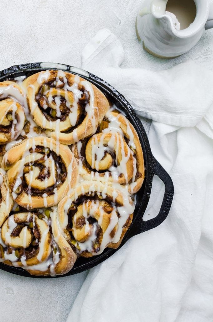 cinnamon rolls baked in cast iron pan drizzled with icing
