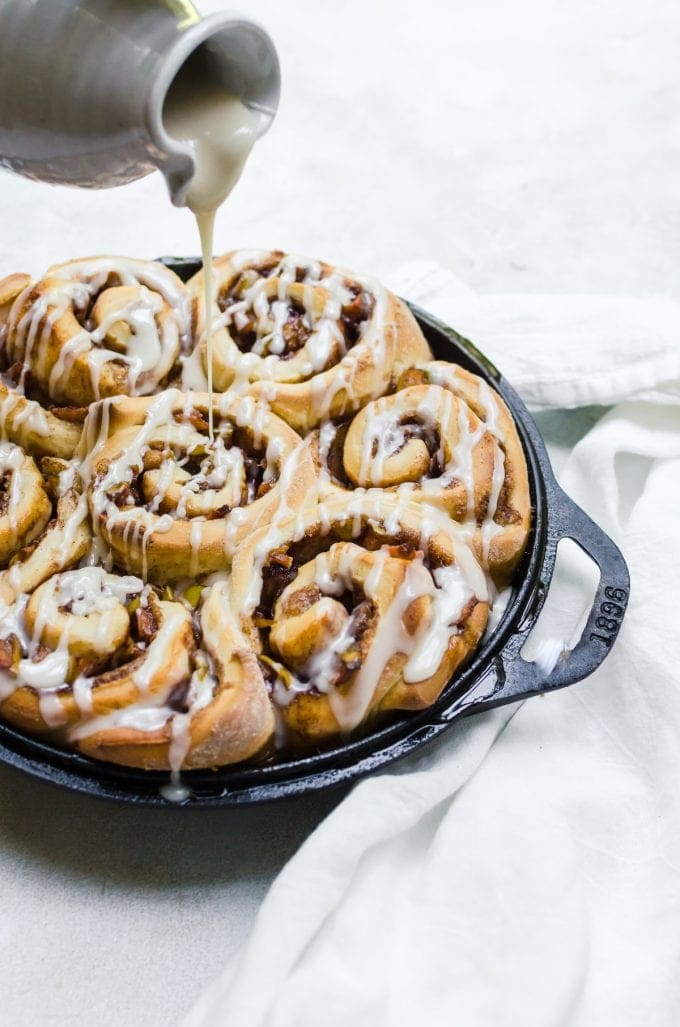 cinnamon rolls being drizzled with icing