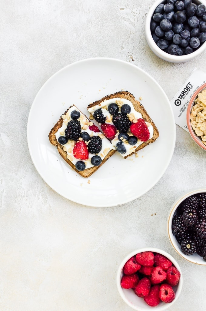 breakfast toast on a white plate with fruit in bowls
