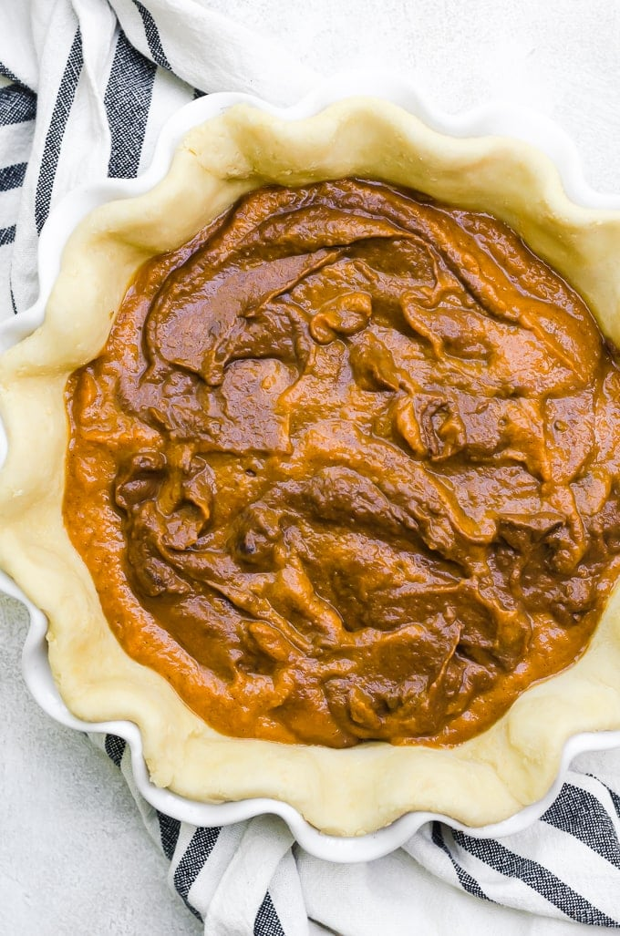 swirls of chocolate pumpkin mix in pie crust