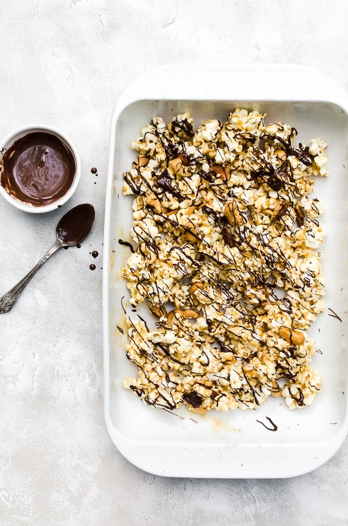 moose munch recipe in a white baking dish with drizzled chocolate
