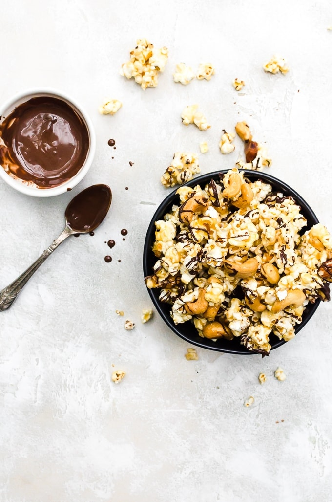 overhead shot moose munch recipe in a black bowl with drizzled chocolate