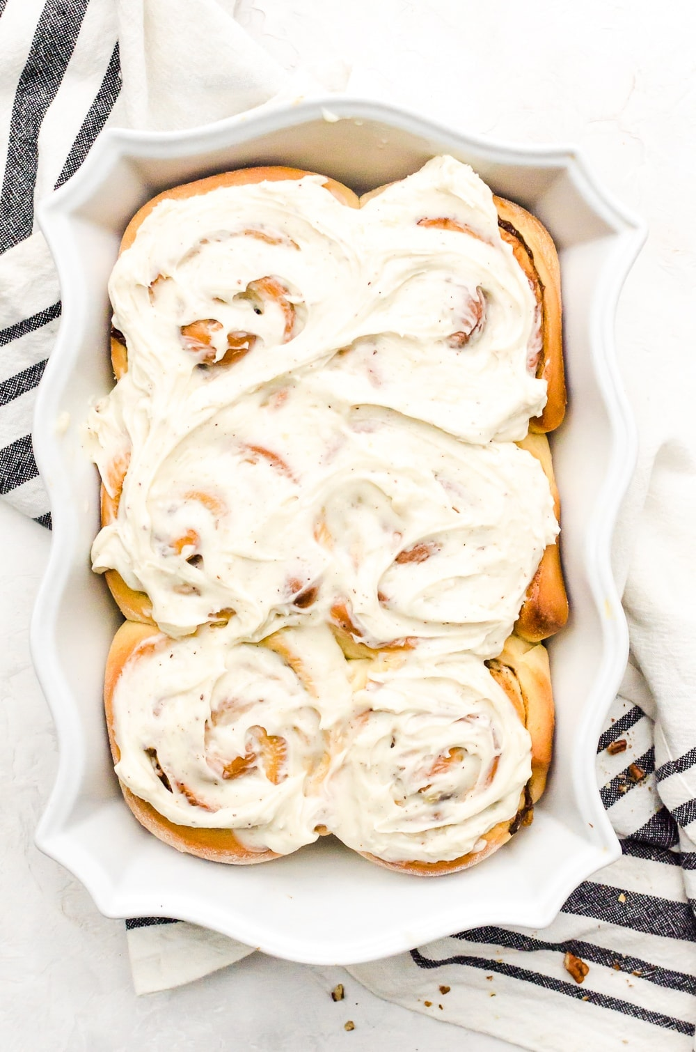pan of banana cinnamon rolls and brown butter cream cheese frosting