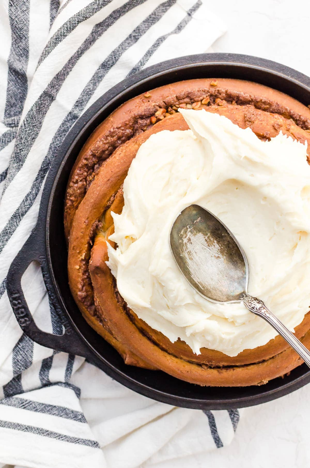 overhead giant cinnamon roll cream cheese icing spread spoon