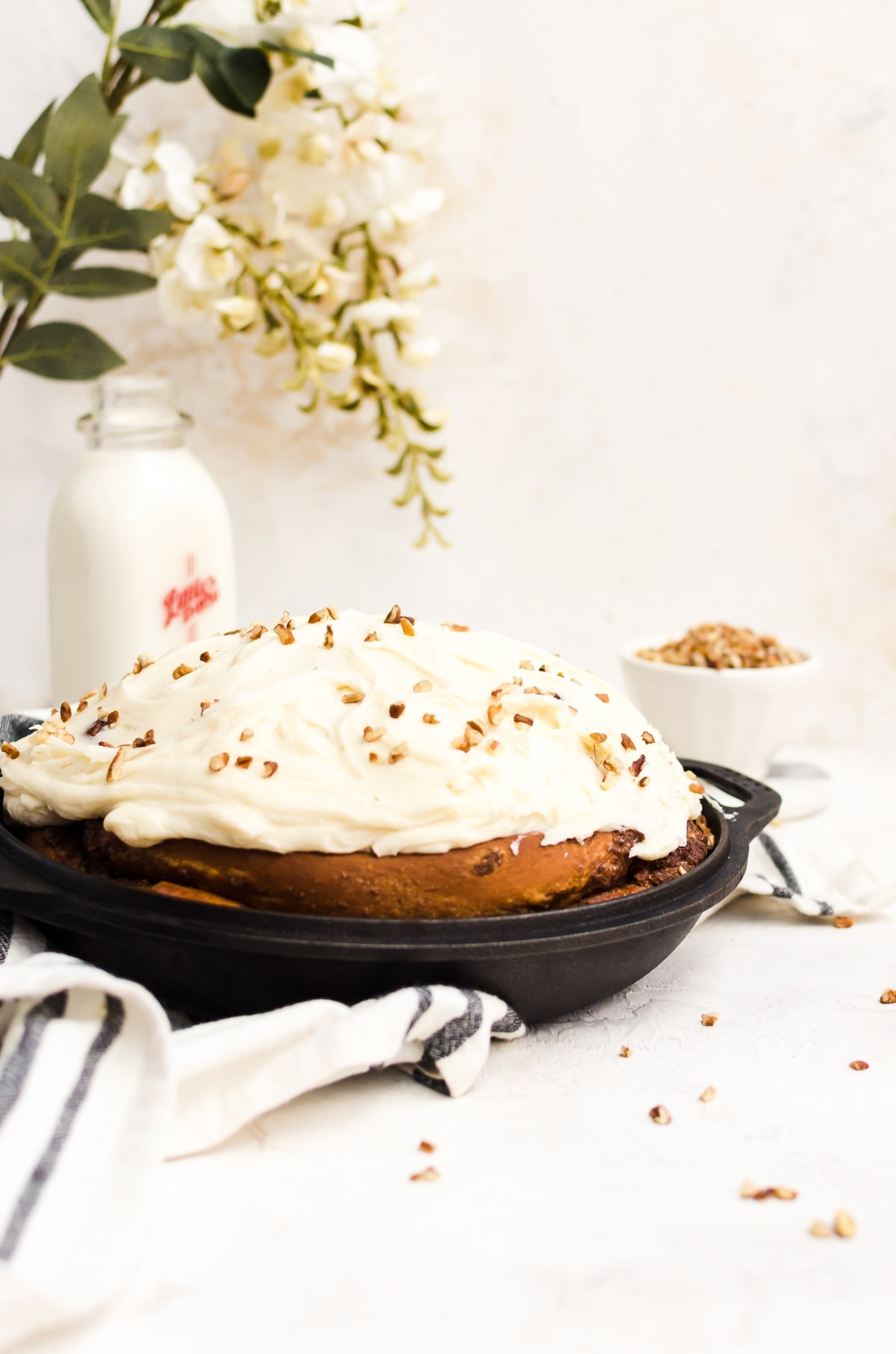 giant cinnamon roll with frosting in cast iron pan