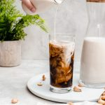 creamy cashew milk poured into glass of iced coffee
