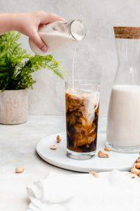 creamy cashew milk poured into glass of iced coffee