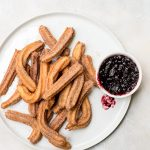 homemade churros on white plate with jam