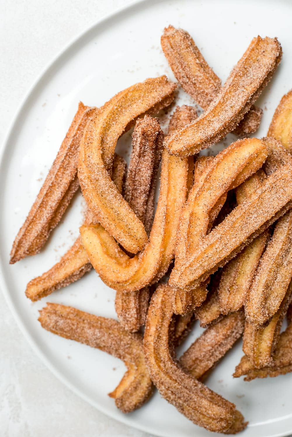 close up homemade churros on white plate