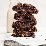 broken giant double chocolate cookies stacked with glass of milk