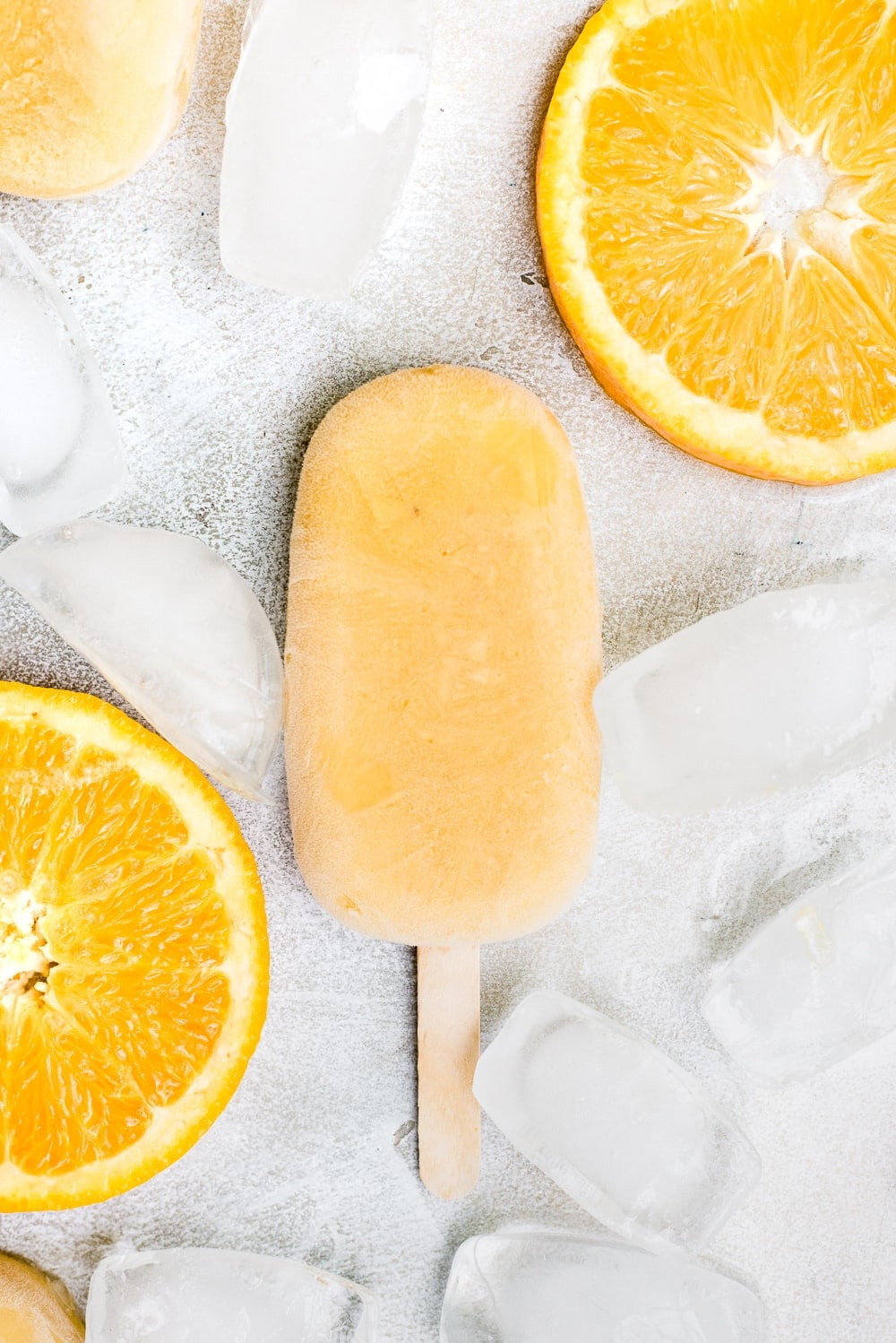 close up orange creamsicle popsicle with ice and orange slices