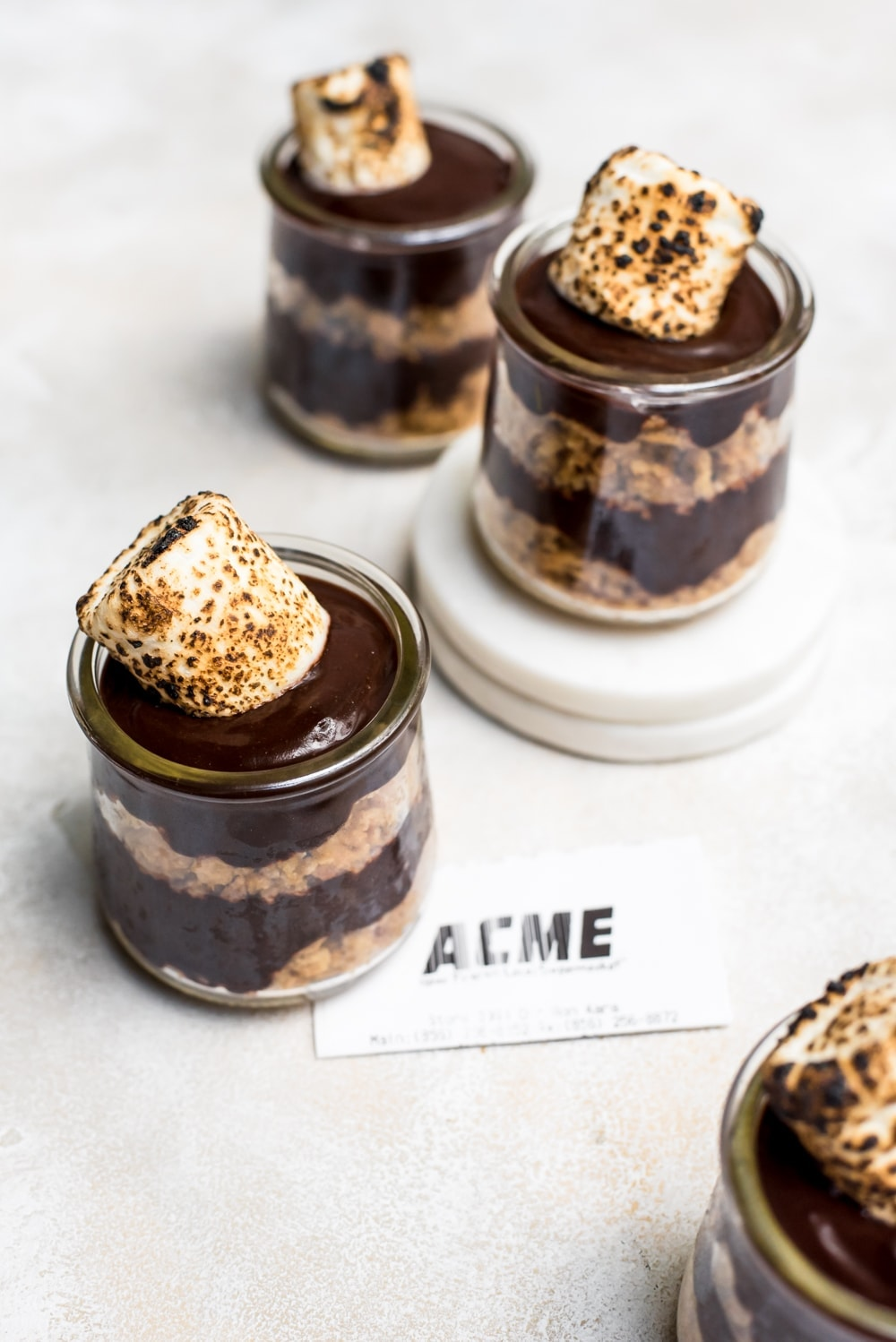 overhead s'mores pudding in jars on marble slabs