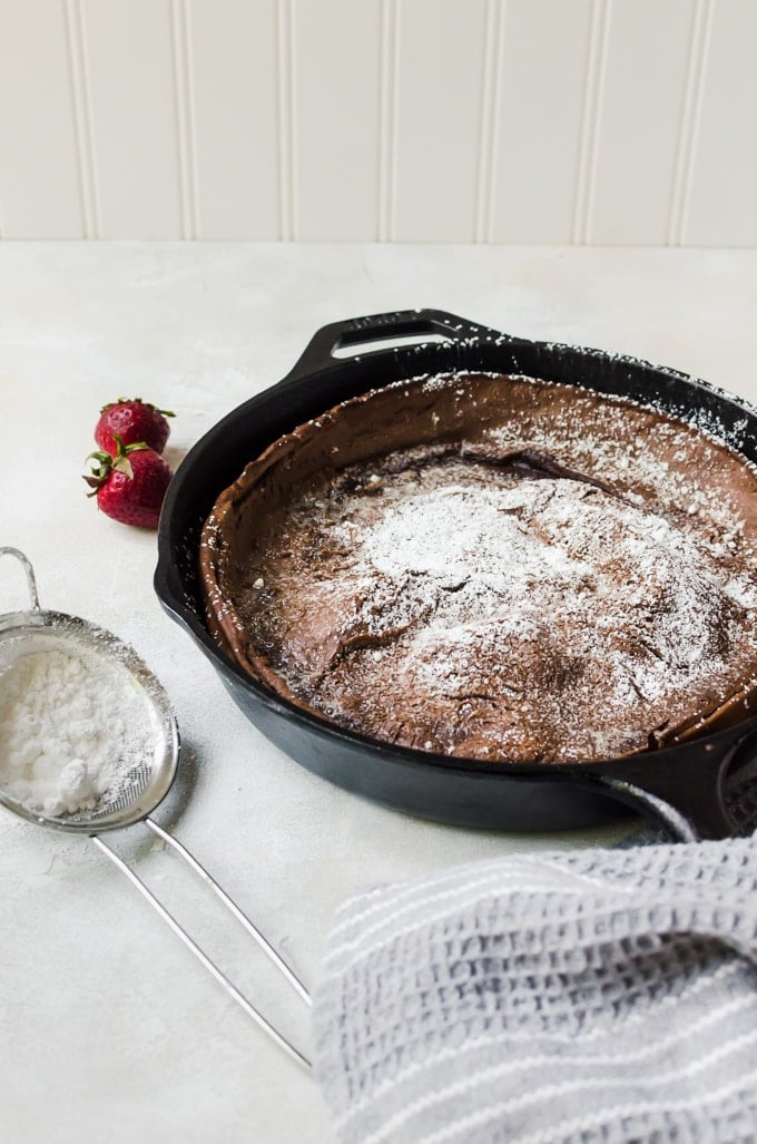 chocolate dutch baby with powdered sugar and strawberries