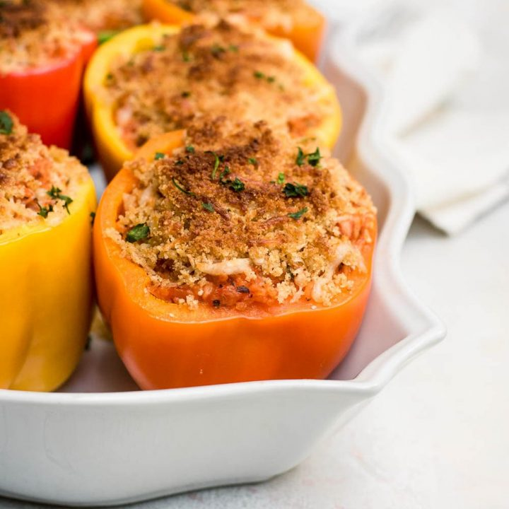 close up italian chicken stuffed peppers in baking pan