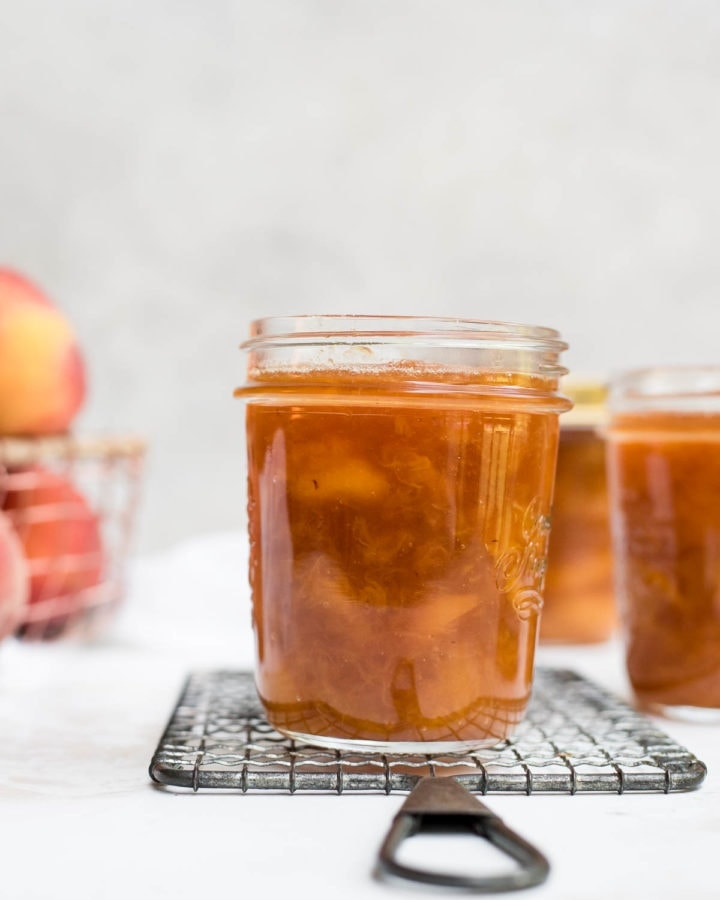peach jam in a jar with peaches in the background
