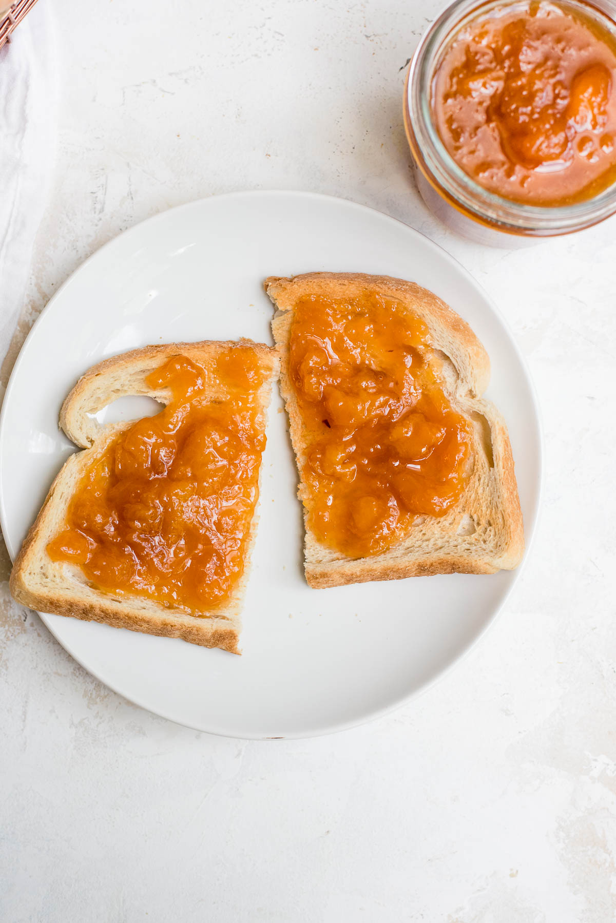 toast cut in half slathered with peach jam
