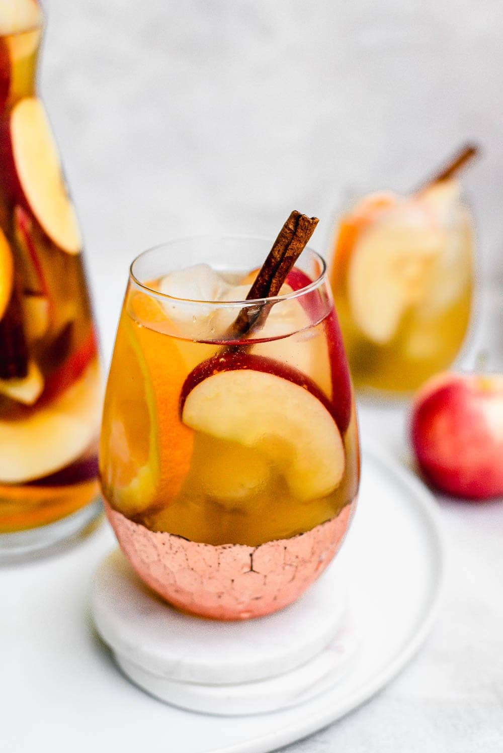 close up apple cider sangria in wine glass with copper bottom