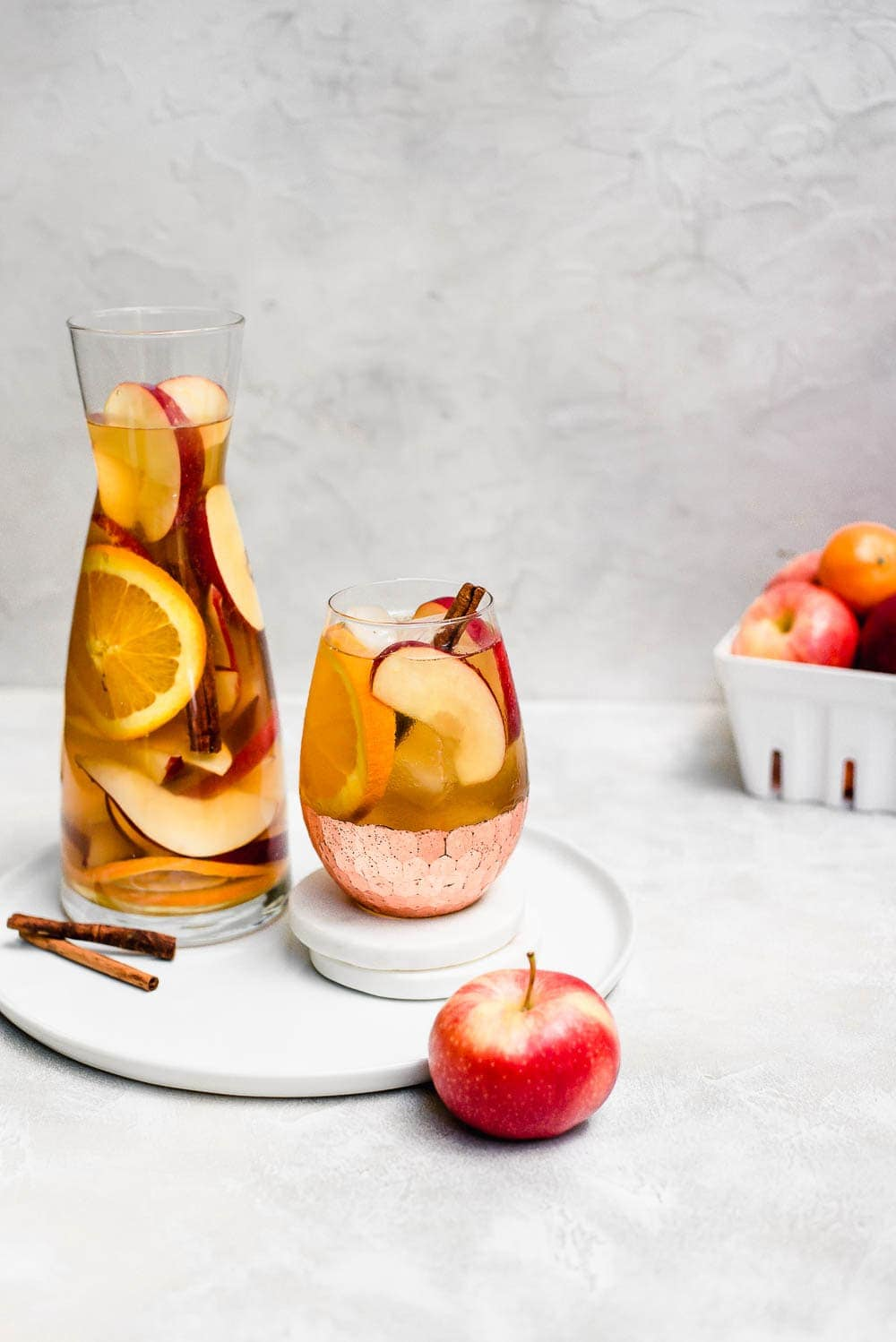 apple cider sangria on serving tray and coasters with apples