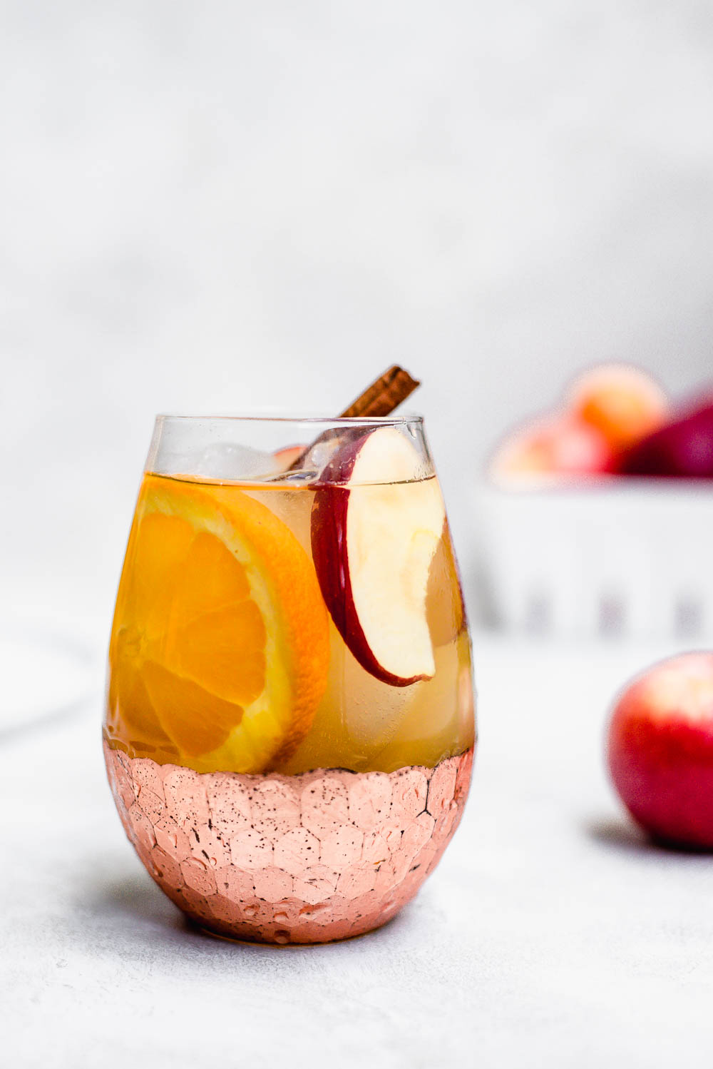 apple cider sangria in glass with cinnamon stick garnish