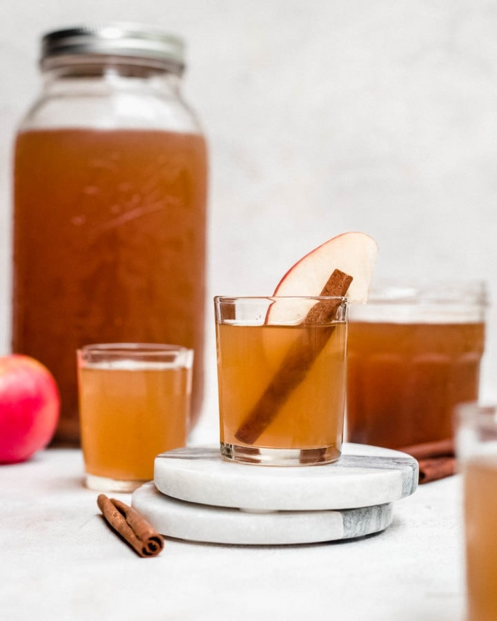apple pie moonshine in shot glasses and mason jar with cinnamon and apples
