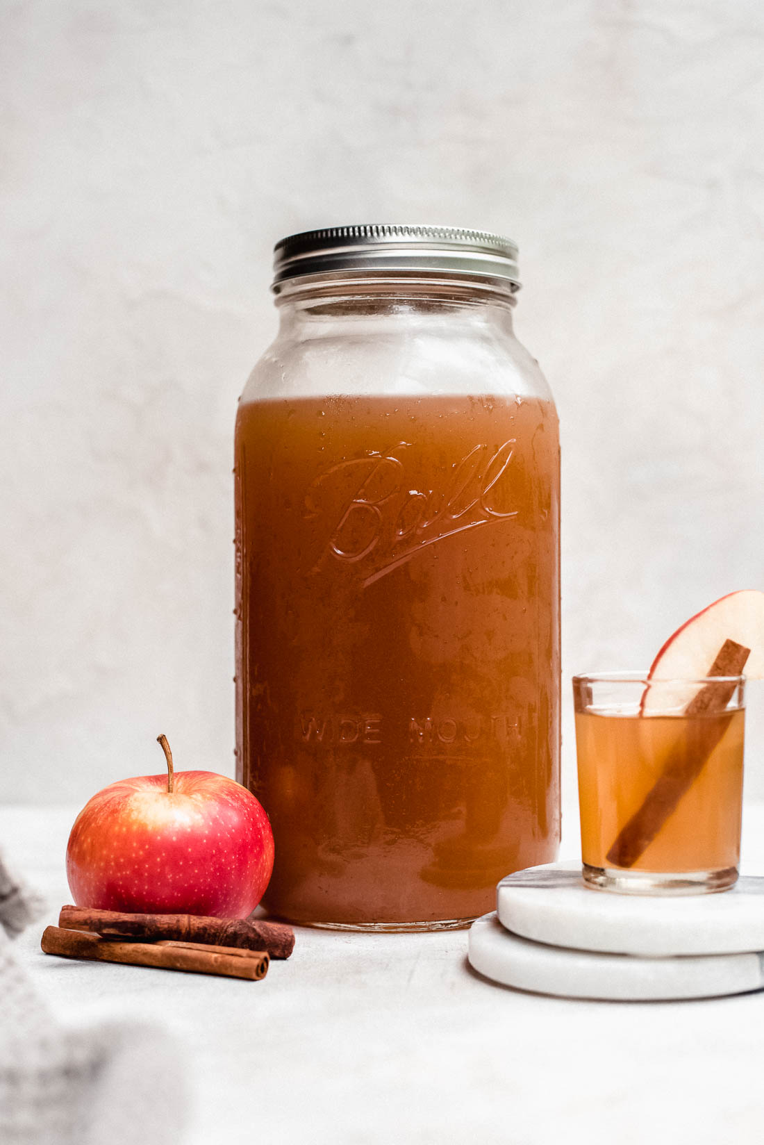 apple pie moonshine in mason jar with apples and cinnamon stick