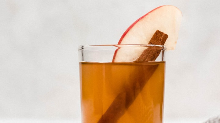 apple pie moonshine in shot glass with apple slice and cinnamon stick