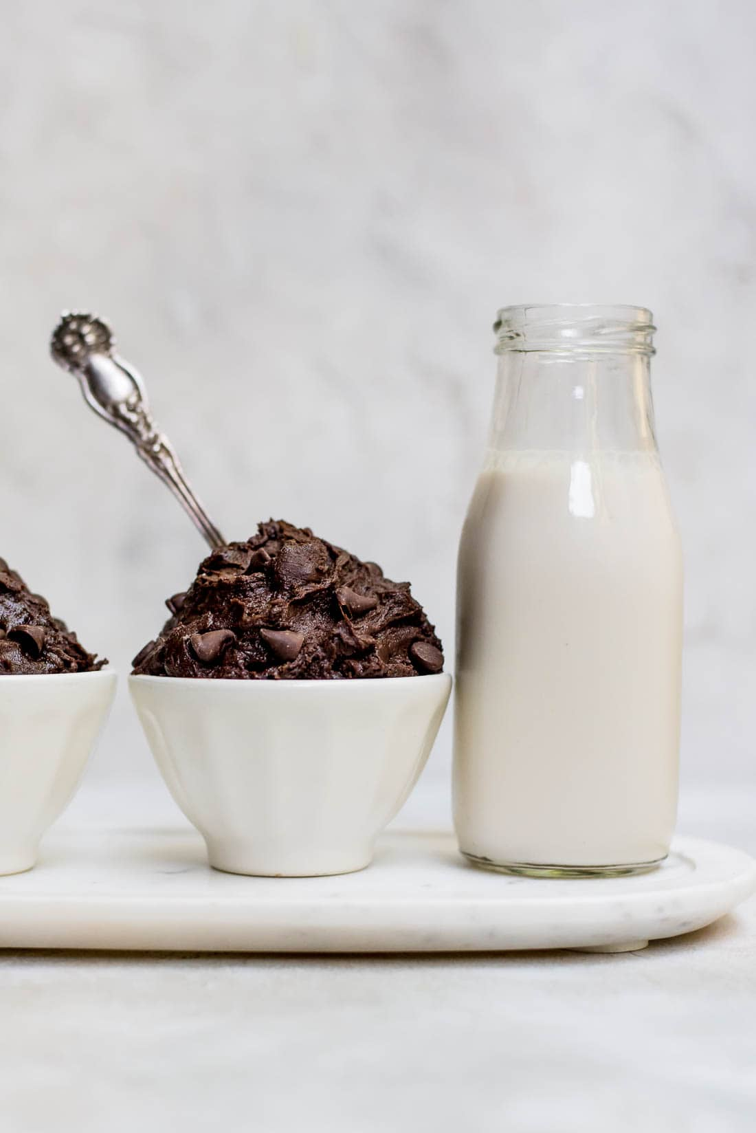 edible brownie batter in white bowl next to milk bottle
