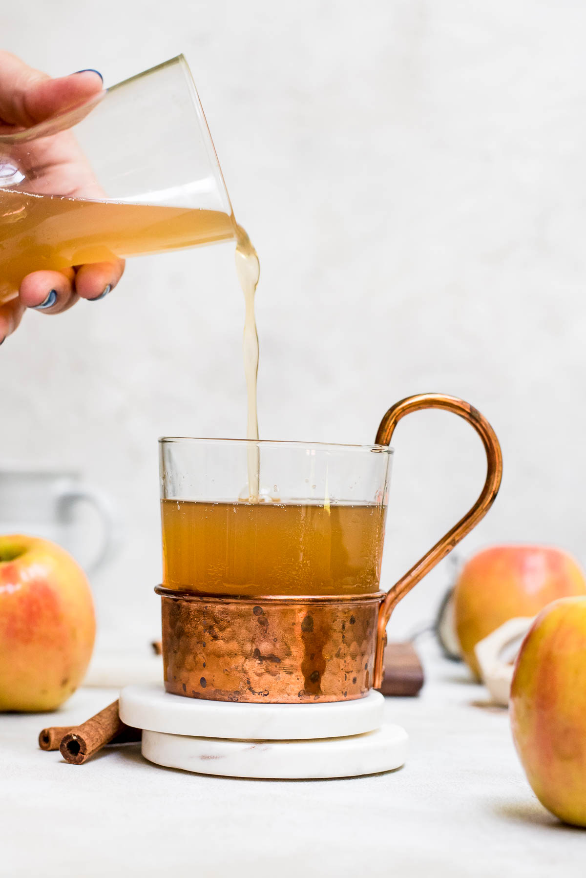 warm homemade apple cider in a glass and copper mug on white marble coaster